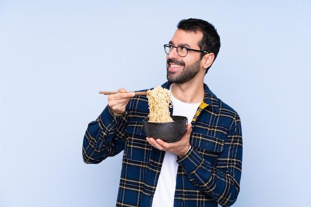 Jonge over een blauwe noedels met eetstokjes houden en mens die over blauwe muur omhoog kijken