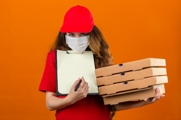 Jonge over gespannen leveringsvrouw die rood poloshirt en pet in medisch beschermend masker draagt en om een handtekening vraagt terwijl hij met stapel pizzadozen over geïsoleerde oranje achtergrond staat
