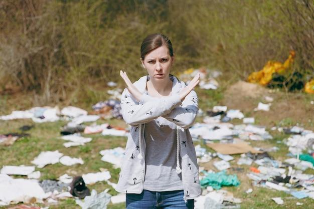 Jonge overstuur bezorgde vrouw in vrijetijdskleding die een stopgebaar toont met gekruiste handen in een bezaaid park