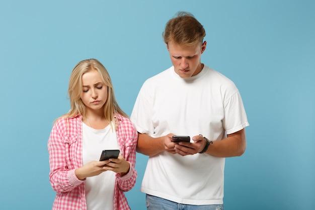 Jonge overstuur paar vrienden man en vrouw in wit roze lege lege t-shirts poseren