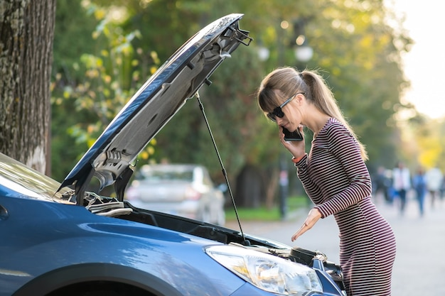 Jonge overstuur vrouwelijke chauffeur praten op mobiele telefoon in de buurt van een kapotte auto met open kap wachten op hulp die problemen heeft met haar voertuig op een stadsstraat.