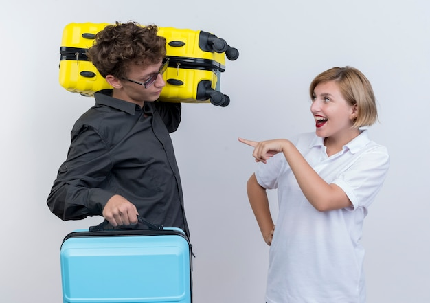Jonge paar toeristen gelukkige vrouw wijzend met wijsvinger op haar ontevreden vriendje met koffers staande over witte muur