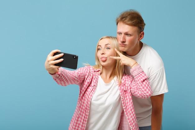 Jonge paar vrienden man en vrouw in wit roze t-shirts poseren