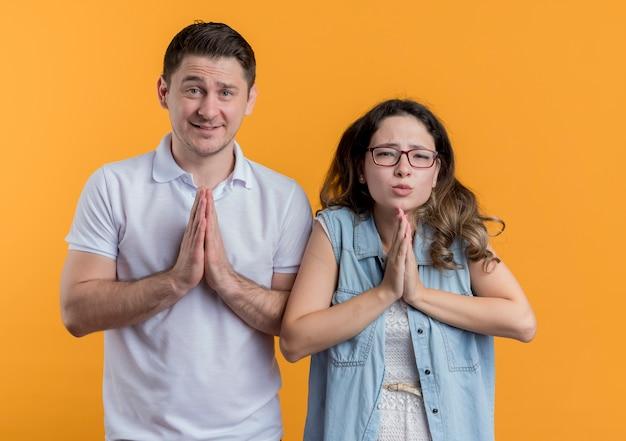 Jonge paarman en vrouw die in vrijetijdskleding palmen houden die wens met hoopuitdrukking maken die zich over oranje muur bevinden