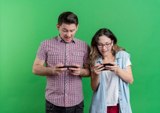 Jonge paarman en vrouw die in vrijetijdskleding smartphones het speelspel houden die zich over groene muur bevinden