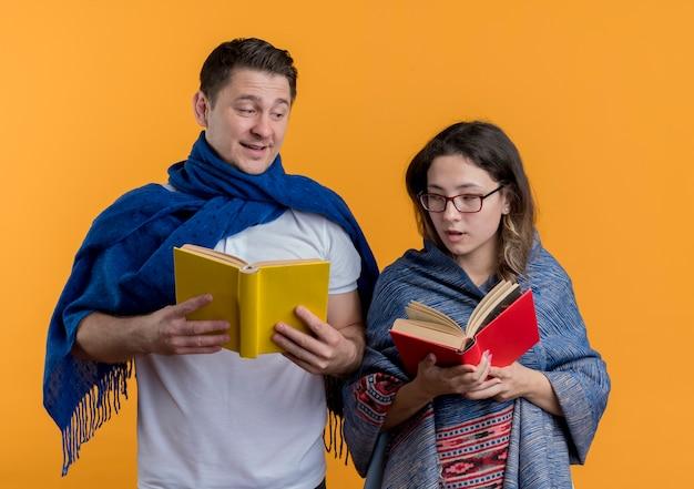 Jonge paarman en vrouw die met dekens boeken het gelukkige en positieve glimlachen houden die zich over oranje muur bevinden