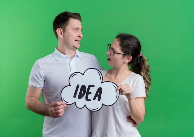 Jonge paarman en vrouw die zich samen glimlachend gelukkig en positief de bellenteken van de holdingstoespraak met woordidee bevinden die elkaar over groene muur bekijken