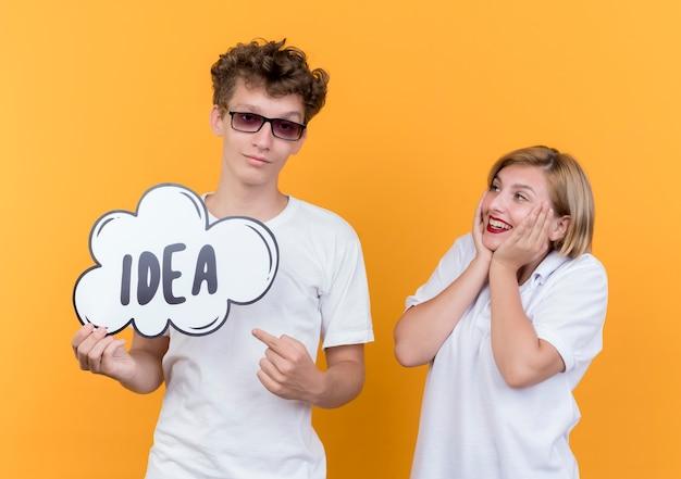 Jonge paarman en vrouw die zich samen glimlachend gelukkig en positief de bellenteken van de holdingstoespraak met woordidee over oranje muur bevinden