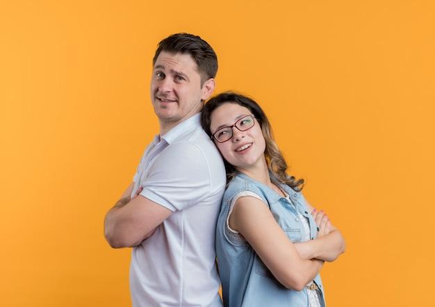 Jonge paarman en vrouw in vrijetijdskleding die zich rijtjes gelukkig en positief bevinden die over oranje muur glimlachen