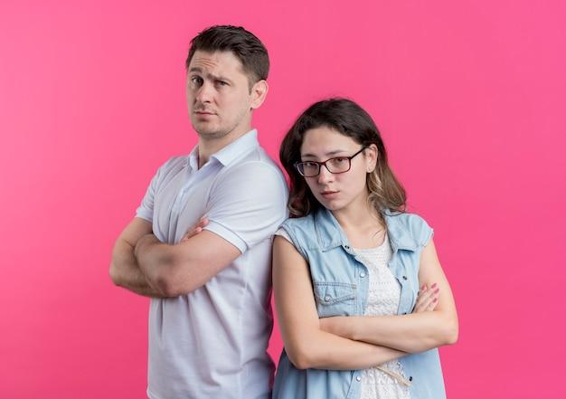 Jonge paarman en vrouw in vrijetijdskleding die zich rijtjes ontevreden en fronsend over roze muur bevinden