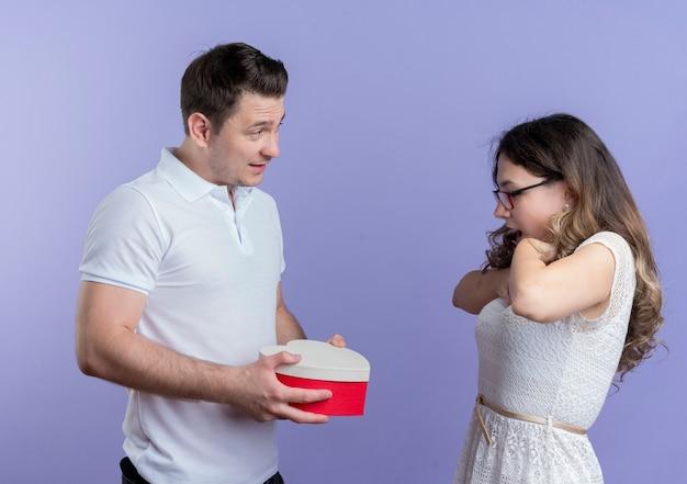 Jonge paarmens die een giftdoos geeft aan zijn verraste geliefde vriendin die zich over blauwe muur bevindt