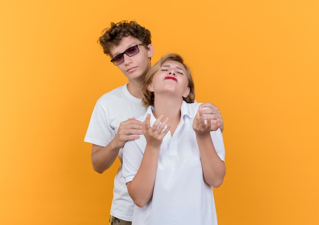 Jonge paarmens die zijn ontevreden en boos vriendin probeert te omhelzen die zich over oranje muur bevindt