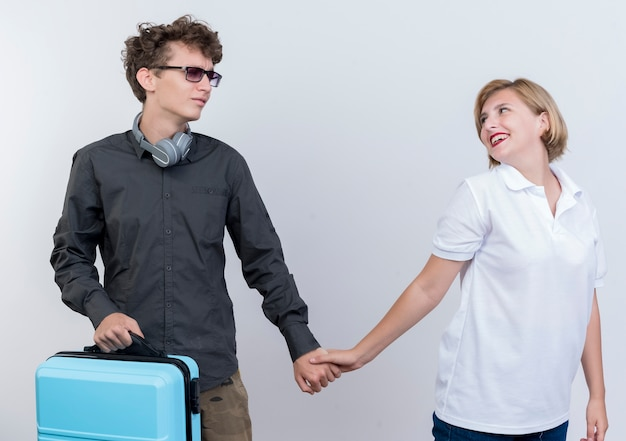 Jonge paarmens met koffer die zijn gelukkige vriendin verlaten die haar hand aanraken die zich over witte muur bevindt