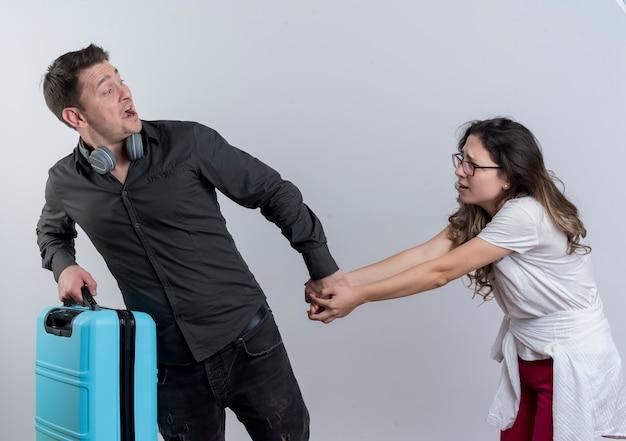 Jonge paarmens met koffer die zijn ongelukkige vriendin verlaten die zich over witte muur bevinden