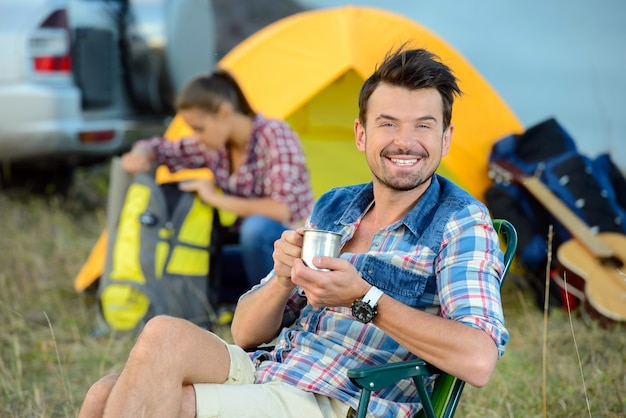 Jonge paartoeristen die thee drinken dichtbij het tentenkamp