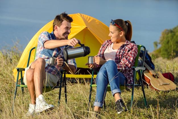 Jonge paartoeristen die thee drinken dichtbij het tentenkamp.
