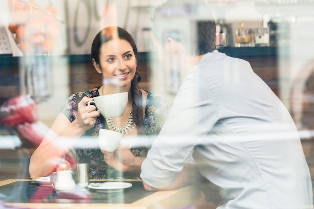 Jonge paarzitting bij een lijst terwijl binnen het drinken van koffie en cappuccino in een koffiewinkel