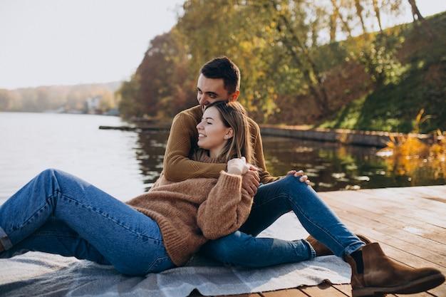 Jonge paarzitting op dekbrug door de rivier