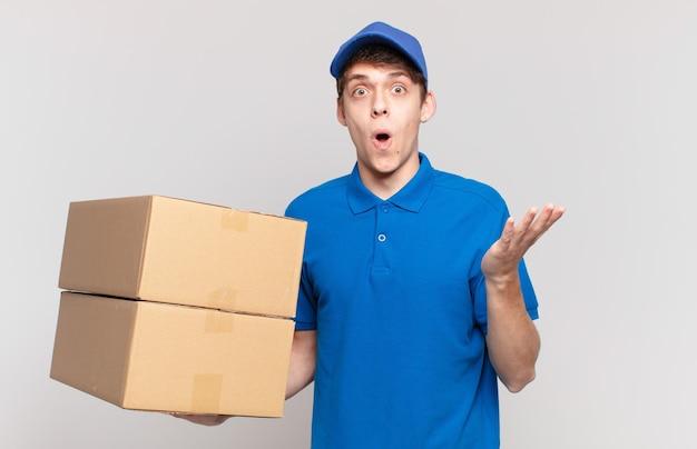 Jonge pakketbezorger jongen met open mond en verbaasd, geschokt en verbaasd met een ongelooflijke verrassing