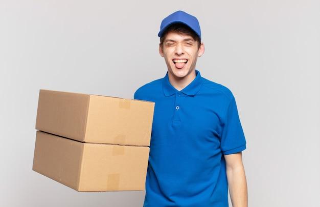 Jonge pakketbezorger met vrolijke, zorgeloze, rebelse houding, grappen maken en tong uitsteken, plezier maken