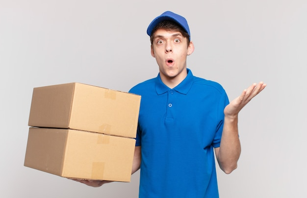 Jonge pakketbezorger voelt zich extreem geschokt en verrast, angstig en in paniek, met een gestrest en geschokte blik