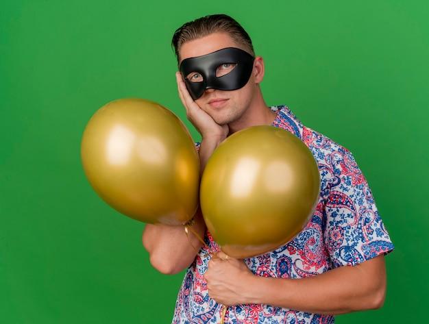 Jonge partijkerel die maskeradeoogmasker draagt dat ballons houdt die hand op wang zetten die op groen wordt geïsoleerd