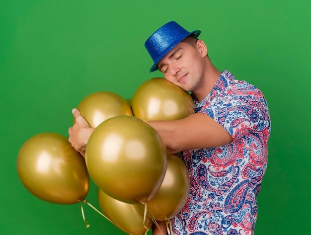 Jonge partijkerel met gesloten ogen die blauwe hoed dragen die zich naast ballons bevinden die op groen worden geïsoleerd