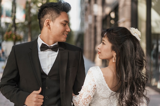 Jonge pasgetrouwden poseren samen buitenshuis