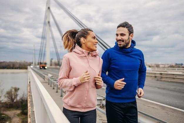 Jonge passen gelukkige sportieve heteroseksuele vrienden die zij aan zij op brug lopen en elkaar bekijken. stedelijk leven concept.