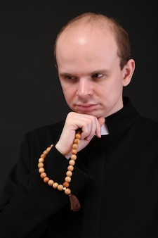 Jonge pastoor met houten rozenkrans, geïsoleerd op zwart
