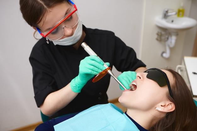 Jonge patiënt in zwarte bril krijgt haar tanden behandeld door vrouwelijke hygiënist met behulp van tandheelkundige uitharding licht