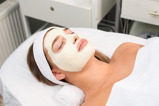 Jonge patiënt lag met gesloten ogen op de bank bij beauty spa salon