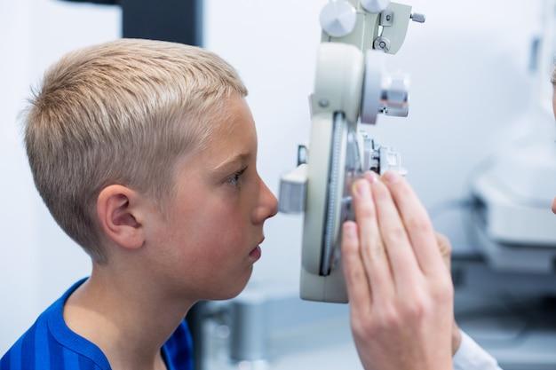 Jonge patiënt ondergaat oogtest door phoropter