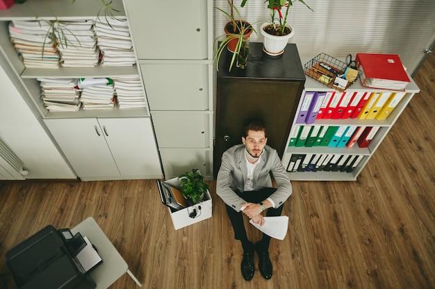 Jonge peinzende failliete makelaar of financieel directeur die met papieren nadenkt over wat hij met zijn bedrijf moet doen na een crisis terwijl hij op de vloer zit