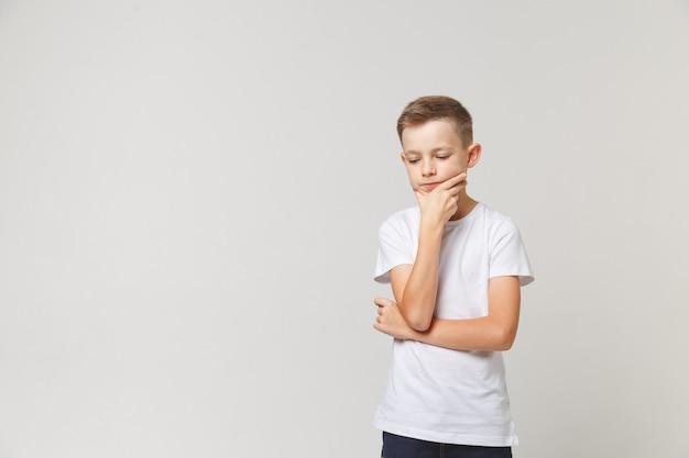 Jonge peinzende jongen die zijn kin op witte achtergrond houdt