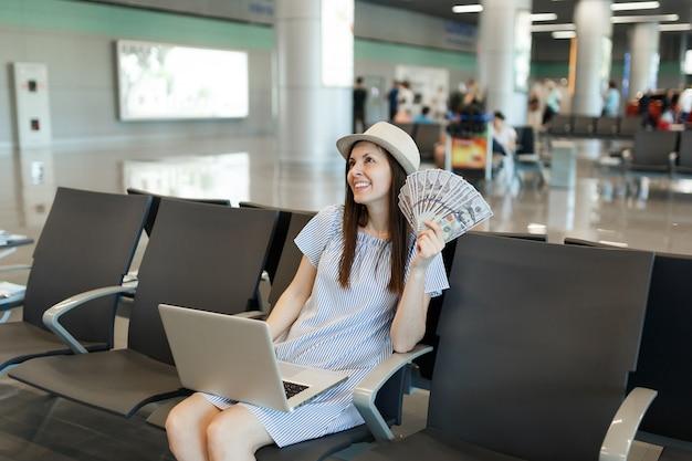 Jonge peinzende reizigerstoeristenvrouw die aan laptop werkt, houdt een bundel dollars contant geld in de lobby op de internationale luchthaven