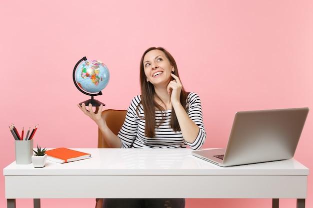 Jonge, peinzende vrouw die een wereldbol vasthoudt, droomt van het plannen van vakantie terwijl ze zit, op kantoor werkt met een moderne pc-laptop