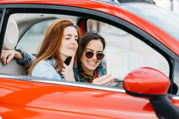 Jonge peinzende vrouw en het glimlachen dameperiezitting in auto en het bekijken kaart