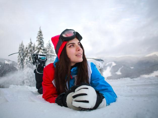 Jonge peinzende vrouw in de winter in sneeuwbos bovenop bergen