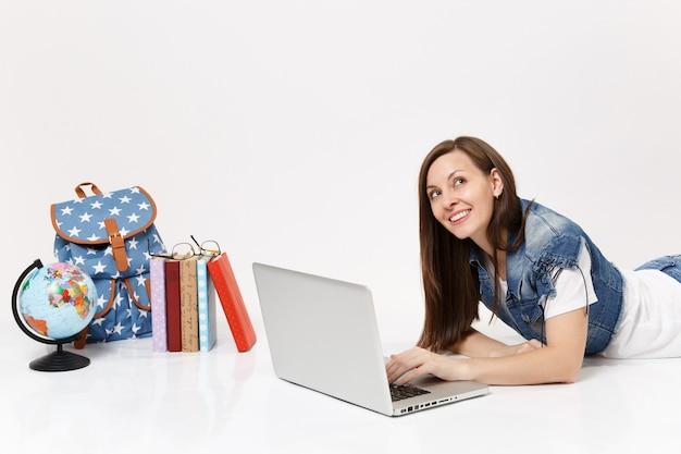 Jonge peinzende vrouw student in denim kleding dromen werken op laptopcomputer liggend in de buurt van globe, rugzak en schoolboeken geïsoleerd