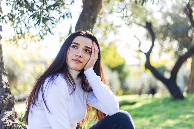 Jonge peinzende vrouwenzitting op park dat weg eruit ziet