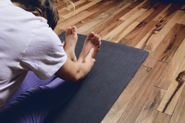 Jonge persoon beoefenen van yoga in huis