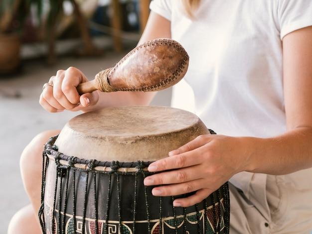 Jonge persoon die afrikaanse slaginstrumenten speelt