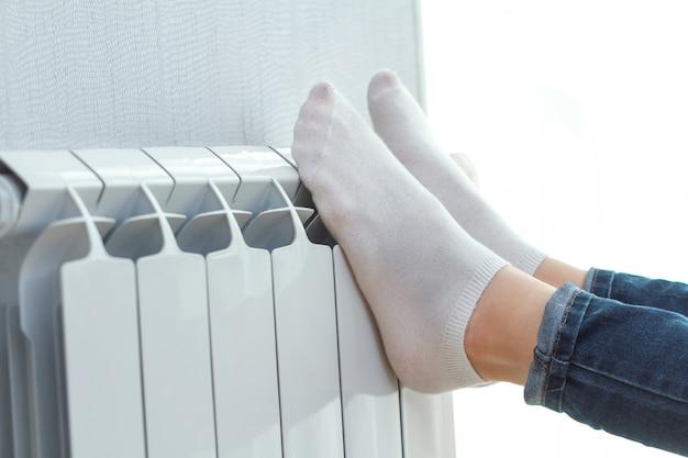Jonge persoon die haar benen thuis op de batterij verwarmt