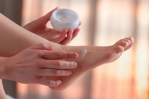 Jonge persoon die om haar voeten geeft en hydraterende, hydraterende crème aanbrengt. voet- en huidverzorging.