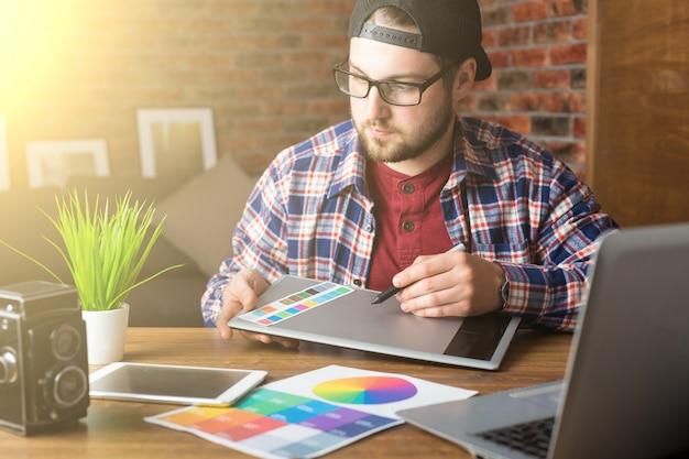Jonge perspectiefontwerper met grafisch tablet in modern bureau