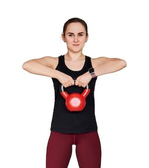 Jonge petite vrouw traint met kettlebell, geïsoleerd op een witte achtergrond