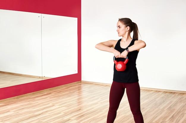 Jonge petite vrouw traint met kettlebell in een ruime sportschool in de spiegel kijken
