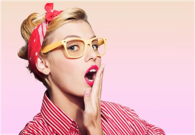 Jonge pin-up blonde vrouw met een bril met geschokte uitdrukking