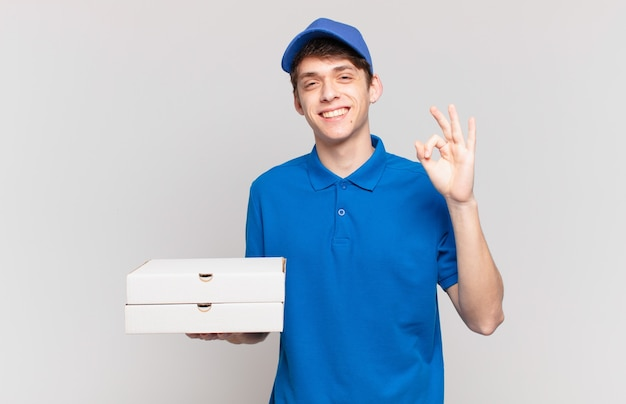 Jonge pizza bezorgt jongen die zich gelukkig, ontspannen en tevreden voelt, goedkeuring toont met een goed gebaar, glimlachend